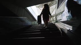 Κορίτσι σκιαγραφιών με τη βαλίτσα που περπατά κάτω απόθεμα βίντεο