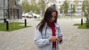 Κορίτσι στην οδό που εξετάζει το smartphone φιλμ μικρού μήκους