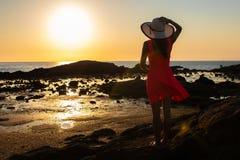 Κορίτσι στους περίπατους καπέλων κατά μήκος της παραλίας στο ηλιοβασίλεμα στοκ φωτογραφίες