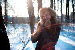 Κορίτσι στο θερμό καπέλο με τα χτυπήματα αυτιών στο υπόβαθρο του χιονιού στοκ εικόνες