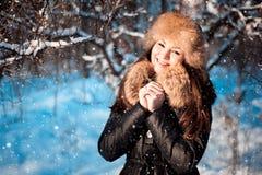Κορίτσι στο θερμό καπέλο με τα χτυπήματα αυτιών στο υπόβαθρο του χιονιού στοκ φωτογραφίες