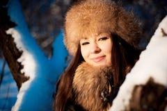 Κορίτσι στο θερμό καπέλο με τα χτυπήματα αυτιών στο υπόβαθρο του χιονιού στοκ φωτογραφία με δικαίωμα ελεύθερης χρήσης