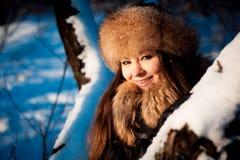 Κορίτσι στο θερμό καπέλο με τα χτυπήματα αυτιών στο υπόβαθρο του χιονιού στοκ εικόνα με δικαίωμα ελεύθερης χρήσης