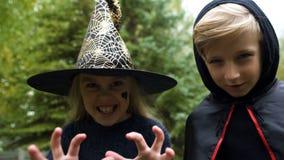 Κορίτσι στο καπέλο μαγισσών και αγόρι στο μανδύα που χαράζουν τη κάμερα, βρυχηθμός απόκοσμος, αποκριές στοκ εικόνες