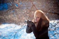 Κορίτσι στο καπέλο με τα χτυπήματα αυτιών που φυσούν στο χιόνι στοκ εικόνες με δικαίωμα ελεύθερης χρήσης