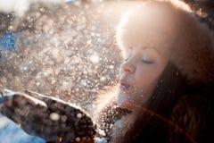 Κορίτσι στο καπέλο με τα χτυπήματα αυτιών που φυσούν στο χιόνι στοκ εικόνα με δικαίωμα ελεύθερης χρήσης