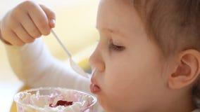 Κορίτσι παιδιών που τρώει το επιδόρπιο στον καφέ Πορτρέτο ενός μωρού που τρώει το παγωτό closeup απόθεμα βίντεο