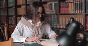 Κορίτσι που μελετά στη βιβλιοθήκη απόθεμα βίντεο