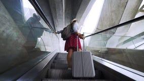 Κορίτσι που οδηγά στην κυλιόμενη σκάλα στο σύγχρονο τερματικό φιλμ μικρού μήκους