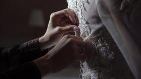 Κούμπωμα της κινηματογράφησης σε πρώτο πλάνο γαμήλιων φορεμάτων νυφών Δίνει τα στερεώνοντας κουμπιά στο νυφικό άσπρο φόρεμα στο ε φιλμ μικρού μήκους