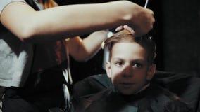 Κούρεμα για το ψαλίδι και τη χτένα αγοριών στον κομμωτή απόθεμα βίντεο