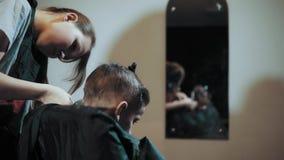 Κούρεμα για trimmer αγοριών για την τρίχα και τη χτένα στον κομμωτή απόθεμα βίντεο