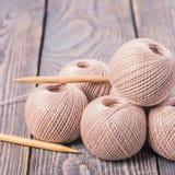 Κουβάρια νημάτων Κουβάρια νημάτων Σφαίρες του νήματος και των πλέκοντας βελόνων για το πλέξιμο σε ένα ξύλινο υπόβαθρο στοκ εικόνες