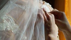 Κουμπιά κουμπιών κινηματογραφήσεων σε πρώτο πλάνο χεριών γυναικών σε ένα γαμήλιο φόρεμα Μια ημέρα γάμου, οι ακτίνες του ήλιου αφο απόθεμα βίντεο