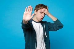Κουρασμένος νεαρός άνδρας στα περιστασιακά ενδύματα που βάζει το χέρι στο μέτωπο, που παρουσιάζει χειρονομία στάσεων με την παλάμ στοκ εικόνες