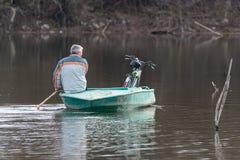 Κουπιά λεμβούχων με ένα ποδήλατο σε μια βάρκα στοκ φωτογραφία
