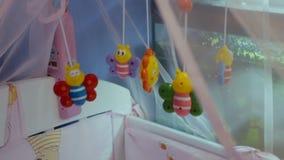 Κρεβάτι με τα παιχνίδια για το νεογέννητο παιδί απόθεμα βίντεο