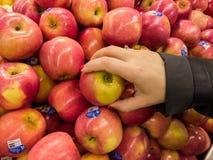Κόκκινα μήλα στο κατάστημα παντοπωλείων με το χέρι γυναικών στοκ φωτογραφία με δικαίωμα ελεύθερης χρήσης