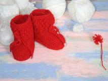 Κόκκινες πλεκτές λείες μωρών, κόκκινες και άσπρες σφαίρες του νήματος μαλλιού για το πλέξιμο και ενός κόκκινου πυροβόλου του νήμα στοκ φωτογραφίες με δικαίωμα ελεύθερης χρήσης