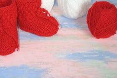 Κόκκινες πλεκτές λείες μωρών, κόκκινες και άσπρες σφαίρες του νήματος μαλλιού για το πλέξιμο σε ένα ροζ - μπλε υπόβαθρο στοκ εικόνα