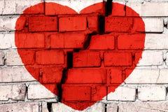 Κόκκινη σπασμένη καρδιά στο τουβλότοιχο με τη μεγάλη ρωγμή στη μέση Έννοια της σπασμένης αγάπης ελεύθερη απεικόνιση δικαιώματος