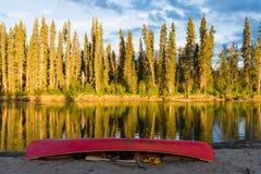 Κόκκινο κανό στην ακτή του ποταμού Yukon Καναδάς Nisutlin στοκ εικόνες με δικαίωμα ελεύθερης χρήσης