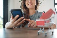 Κόκκινο κιβώτιο δώρων στο κάρρο αγορών με τις γυναίκες που χρησιμοποιούν το κινητό τηλέφωνο στοκ εικόνες
