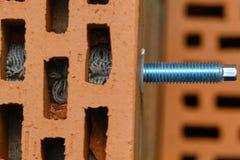 Κόκκινο κοίλο τούβλο πλινθοδομής Εγκατάσταση μιας χημικής άγκυρας που χρησιμοποιεί ένα ειδικό εργαλείο - γωνία ρητίνης, μανικιών  στοκ φωτογραφίες