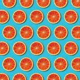 Κόκκινο πορτοκαλί σχέδιο φετών τοπ άποψης στο δονούμενο τυρκουάζ υπόβαθρο στοκ εικόνα