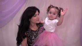 Κόρη μωρών με τη μητέρα της που κυματίζει τα χέρια της στη κάμερα απόθεμα βίντεο