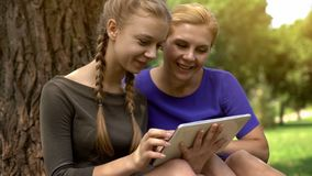 Κόρη που παρουσιάζει φωτογραφίες μητέρων του φίλου της, που χρησιμοποιεί την ταμπλέτα, κοινωνική δικτύωση στοκ εικόνα με δικαίωμα ελεύθερης χρήσης