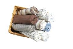 Κυλημένες επάνω πετσέτες υφάσματος στο καλάθι που απομονώνεται στοκ φωτογραφία