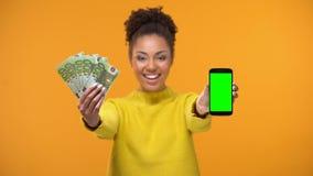 Κυρία αφροαμερικάνων που παρουσιάζει το smartphone και δέσμη των ευρώ, μεταφορά χρημάτων απόθεμα βίντεο
