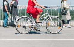 Κυρία σε ένα ποδήλατο Το κορίτσι στο κόκκινο φόρεμα που οδηγά ένα ποδήλατο γύρω από την πόλη στοκ εικόνες με δικαίωμα ελεύθερης χρήσης