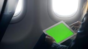 Κυρία που κρατά την ταμπλέτα της στα χέρια και που κάθεται στο αεροπλάνο απόθεμα βίντεο