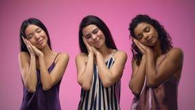 Κυρίες στις πυτζάμες που παρουσιάζουν χειρονομία ύπνου, άνετος ύπνος, γλυκά όνειρα απόθεμα βίντεο