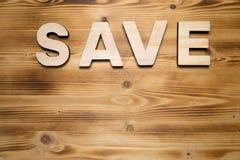 Λέξη SAVE που γίνεται με τις δομικές μονάδες στον ξύλινο πίνακα στοκ φωτογραφίες