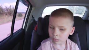 Λίγα το κουρασμένο αγόρι κάθονται στο κάθισμα των πίσω ειδικών παιδιών απόθεμα βίντεο