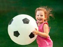 Λίγο κοριτσάκι τρέχει με μια τεράστια σφαίρα ποδοσφαίρου Το κορίτσι χαίρεται και χαμογελά στοκ φωτογραφίες με δικαίωμα ελεύθερης χρήσης
