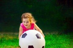 Λίγο κοριτσάκι που παίζει με μια τεράστια σφαίρα ποδοσφαίρου στοκ φωτογραφία με δικαίωμα ελεύθερης χρήσης