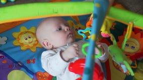 Λίγο μωρό που παίζει με τα παιχνίδια στο χαλί απόθεμα βίντεο