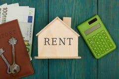 """λίγο σπίτι με το κείμενο """" Rent"""" , κλειδιά, υπολογιστής, διαβατήριο, χρήματα στο μπλε ξύλινο γραφείο στοκ εικόνα με δικαίωμα ελεύθερης χρήσης"""