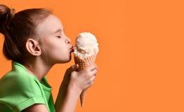 Λίγο παγωτό βανίλιας φιλήματος παιδιών κοριτσάκι στον κώνο βαφλών στο κίτρινο πορτοκαλί υπόβαθρο στην πράσινη μπλούζα στοκ εικόνες με δικαίωμα ελεύθερης χρήσης