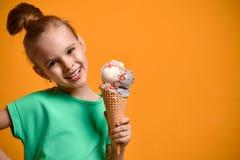 Λίγο παιδί κοριτσάκι που τρώει το παγωτό βανίλιας στον κώνο βαφλών στο κίτρινο υπόβαθρο απαγορευμένα στοκ φωτογραφία με δικαίωμα ελεύθερης χρήσης