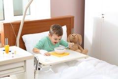 Λίγο παιδί με την ενδοφλέβια σταλαγματιά που τρώει τη σούπα στοκ φωτογραφία