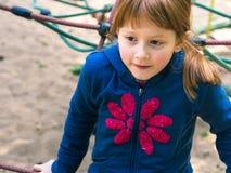Λίγο redhead κορίτσι που παίζει στην παιδική χαρά στοκ φωτογραφίες