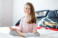 Λατρευτό ευτυχές κορίτσι παιδάκι μετά από να κοιμηθεί στο άσπρο κρεβάτι του ζωηρόχρωμο nightwear Παιδί σχολείου που κάνει τη γιόγ στοκ εικόνες