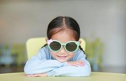 Λατρευτό λίγο ασιατικό κορίτσι παιδιών που βάζει στα παιδιά παρουσιάζει τη φθορά των γυαλιών ήλιων με το χαμόγελο και την εξέταση στοκ εικόνα