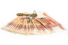 λευκό μετρητών ανασκόπηση&s Τα κλειδιά για το διαμέρισμα στα χρήματα Bill 5 χιλιάες ρούβλια, που διαδίδονται έξω όπως έναν ανεμισ στοκ εικόνες