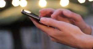 Λεπτά θηλυκά χέρια που τυλίγουν κάτι στο τηλέφωνο κυττάρων Φω'τα βραδιού στο υπόβαθρο Κινηματογράφηση σε πρώτο πλάνο απόθεμα βίντεο